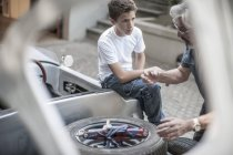 Grandfather and grandson restoring a car together — Stock Photo