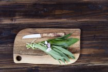 Top view of fresh ramson and daisies on chopping board — Stock Photo