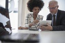Geschäftsmann und Frau mit digitalem Tablet und Taschenrechner — Stockfoto