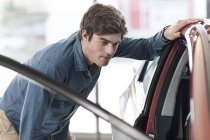 Молодий чоловік, дивлячись на нову машину в автосалону — стокове фото