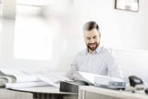 Man in office looking at construction plan — Stock Photo