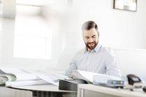 Hombre en la oficina mirando el plan de construcción - foto de stock