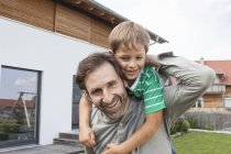 Portrait of happy father carrying son in garden — Stock Photo