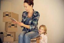 Lachende Frau mit Tochter Blick auf digital-Tablette mit Karton Kisten im Hintergrund — Stockfoto