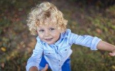 Portrait de petit garçon blond souriant levant les yeux vers la caméra — Photo de stock