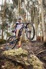 Motociclista della montagna sorridente nella foresta — Foto stock