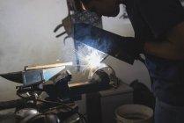 Forger welding metal in workshop — Stock Photo