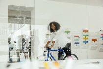 Lächelnde junge Frau mit dem Fahrrad im Büro — Stockfoto
