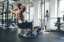Physical athlete exercising with cable machine in gym — Stock Photo