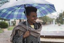 Lächelnde Frau mit Regenschirm an einem regnerischen Tag — Stockfoto