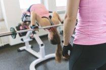 Женщина делает взвешенные расширения спины в спортзале — стоковое фото