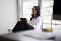 Femme d'affaires de travailler pieds nus sur le plancher dans le bureau moderne — Photo de stock