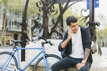 Teenager with a fixie bike sitting in the city talking on phone — Stock Photo