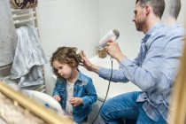 Father drying daughter hair with hairdryer in bathroom — Stock Photo