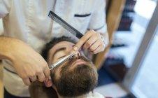 Barber cutting beard of a customer — Stock Photo