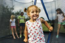 Portrait of toddler girl on trampoline with friends in background — Stock Photo