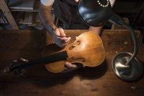 Luthier регулювання звуку пост скрипка в його майстерні — стокове фото
