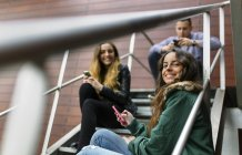 Jovens adultos andando com smartphones nas escadas — Fotografia de Stock
