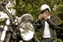 Uomo sorridente in casco moto scattare foto della sua moto — Foto stock