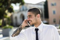Smiling young businessman telephoning with smartphone — Stock Photo