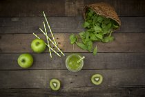 Glass of apple kiwi spinach smoothie and ingredients on dark wood with upturned basket — Stock Photo