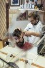 Barber cutting hair of a customer in barbershop — Stock Photo