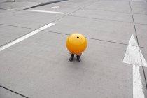 Kleines Mädchen in der Straße hocken, versteckt unter orange sprere — Stockfoto