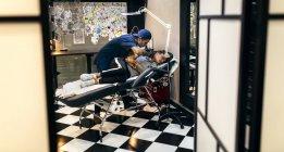 Женщина, делающая татуировку в студии татуировки — стоковое фото