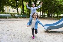 Pai correndo com a filha no playground — Fotografia de Stock