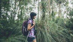 Jeune femme souriante avec sac à dos marchant dans la forêt — Photo de stock