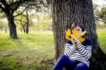 Girl with autumn leaves sitting near tree trunk — Stock Photo