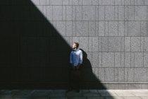 Бизнесмен, стоящий перед серой стеной — стоковое фото