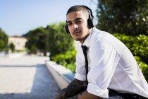 Jeune homme d'affaires avec casque assis sur un mur à la lumière du soleil — Photo de stock