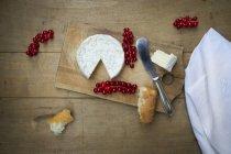 Camembert, pane e ribes rosso su legno — Foto stock