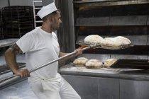Panadero sacando el pan recién hecho del horno de panadería - foto de stock
