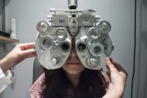 Ophthalmologist adjusting an optometrist phoropter, ready for eye calibration of a patient — Stock Photo