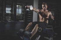 Atleta di fisica che si esercita con i dumbbells in palestra — Foto stock