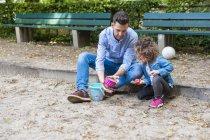 Отец играет с дочерью в песочнице — стоковое фото