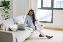 Jeune femme assise sur le canapé à la maison regardant ordinateur portable — Photo de stock