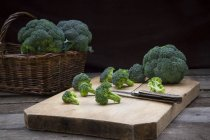 Flores de brócoli sobre tabla de cortar de madera con cuchillo - foto de stock