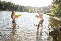 Молодая пара в озере, брызгающаяся водомётами — стоковое фото