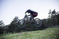 Mountainbiker riding downhill and jumping midair — Stock Photo