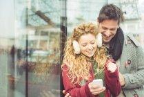 Coppia felice guardando smartphone — Foto stock