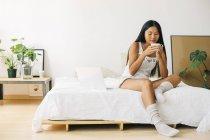 Jeune femme assise sur le lit buvant du café — Photo de stock