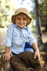 Portrait of smiling blond little boy wearing hat sitting on dead wood — Stock Photo