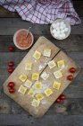 Tagliatelle fatte in casa, ravioli, ripieni di pomodoro mozzarella sul tagliere — Foto stock