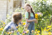 Mother and daughter picking flowers in field — Stock Photo