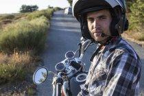 Uomo in casco che si siede su una moto sulla strada aperta — Foto stock