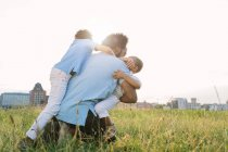 Happy african american playful father with two sons in field — Stock Photo