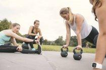 Cuatro mujeres que tienen entrenamiento de campamento de arranque al aire libre - foto de stock